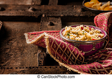 Jeweled Couscous in Ornate Dish on Wooded Table - Still Life...
