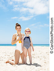 Happy mother applying sunscreen on child in swimsuit at...