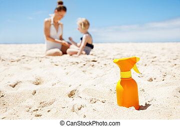Closeup on sunscreen bottle on beach. Family in background -...