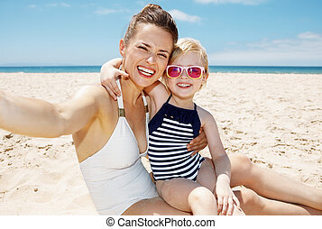 Smiling mother and daughter in swimsuits taking selfies at...
