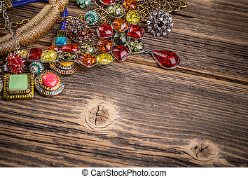 Colorful stones necklaces on wooden surface, space for text