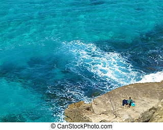 relaxed seaside angler - relaxed angler waiting on a rock by...