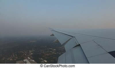 wing of airplane flying above city - travel, transportation,...