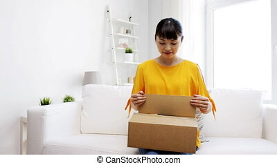 happy asian young woman with parcel box at home