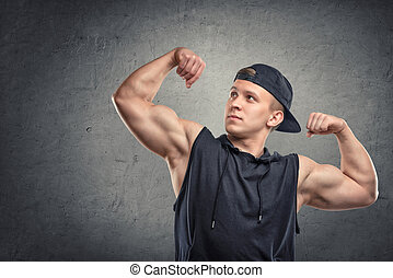 Portrait of young muscular man flexing his biceps and...