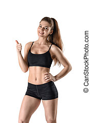 Smiling fitness woman in shorts and a tank top stands...