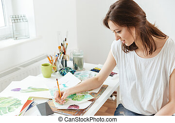Woman artist drawing at the table in workshop - Beautiful...