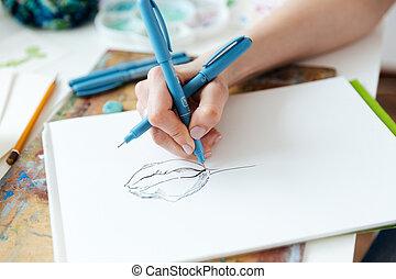Woman artist hands drawing with gel ink pen in sketchbook -...