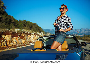 Beautiful pin up woman sitting in cabriolet, enjoying trip...