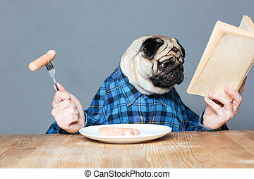 Man with pug dog head eating sausages and reading book -...