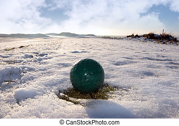 green golf ball on cloudy snow covered golf course - green...