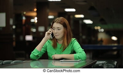 The beautiful woman is sitting at the table in cafe and talking on the cell phone of white color.