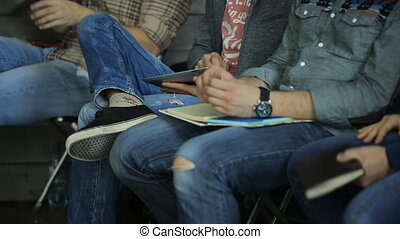 Young people sitting in a row, keep on their laps notebooks, smartphones and tablets