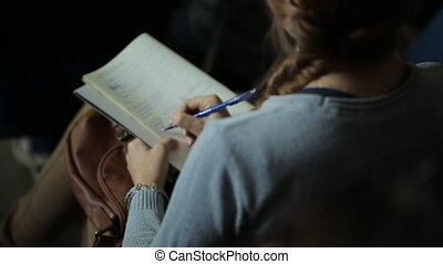 Young woman holds a notebook on her lap, and something writes fast