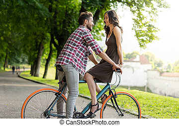 beautiful couple riding a city bike and smiling to each...