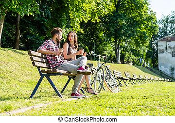 friends taking a rest from biking in park