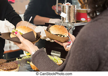 Beef burgers being served on street food stall - Beef...