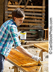 Woman applying fresh wood treatment paint - Woman applying...