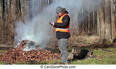 Park Ranger with tablet PC near bonfire
