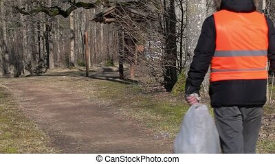 Man with bag picks up plastic - Man with bag pick up empty...