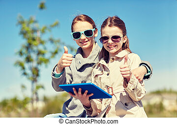 happy girls with tablet pc showing thumbs up