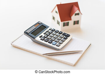 close up of home model, calculator and notebook - building,...