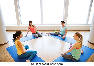 happy pregnant women sitting on mats in gym - pregnancy,...