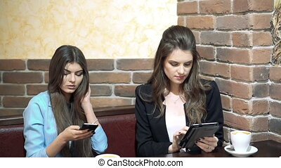 Girls sitting in cafe , sharing news with smartphone