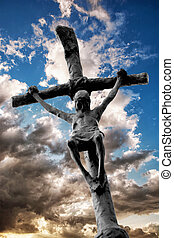 Jesus Christ on the cross with dramatic sky behind him....
