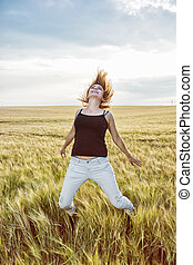 Crazy caucasian woman is jumping in the wheat field, beauty...