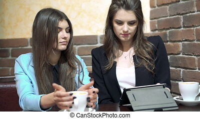 Girls sitting in cafe , sharing news, drinking coffee