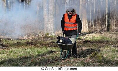 Man pushing wheelbarrow - Man pushing wheelbarrow and start...