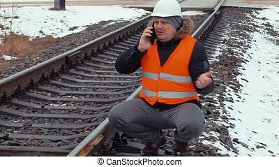 Angry railroad worker talking on cell phone near railway