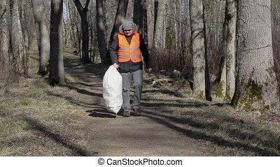 Man with smart phone and bag of plastic bottles on path