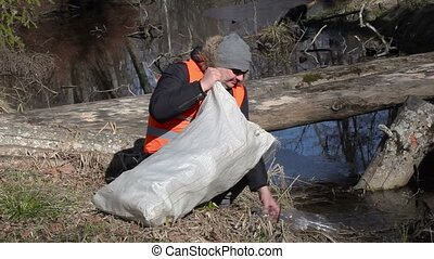 Man with bag picking up empty plastic - Man with bag pick up...