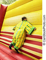 The boy in colorful plastic dress in the bouncy castle...