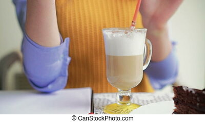 Girl drinking latte, speaking on the phone, using notebook....
