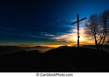 Summit cross a mountain at sunset