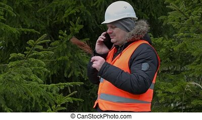 Forest worker with withered branch and smartphone in forest