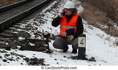 Railroad worker with documentation talking on smart phone...