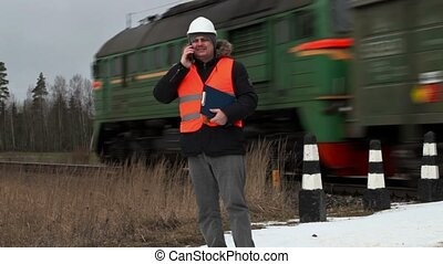 Railroad worker talking on smart phone near railway crossing...