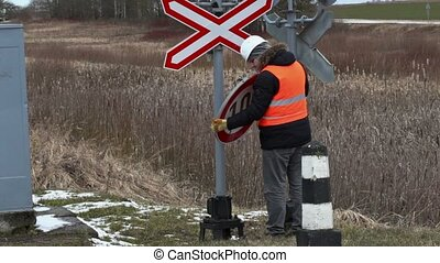 Railroad worker with road sign near railway