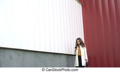 Style lady going outdoor, speaking on the phone, holding...