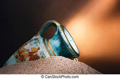 Old blue vase in sands