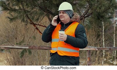 Forest worker with coffee and smartphone near juniper