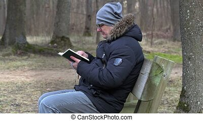Man reading Bible and praying on bench in the park