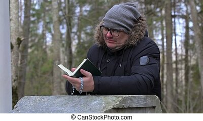 Man with Bible and rosary near pedestal