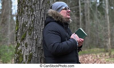 Man with Bible and rosary praying near tree