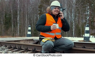Railroad worker with coffee and smartphones on railway