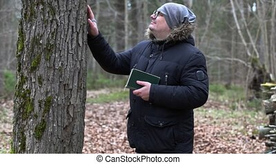 Man with Bible and rosary near tree in the park
